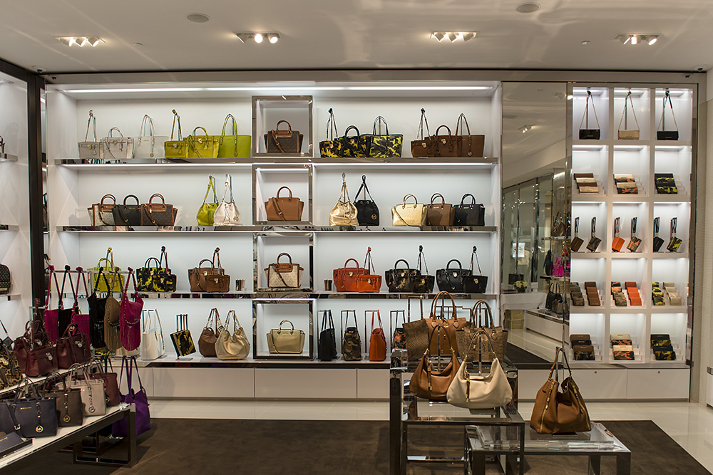 Handbags from the MICHAEL Michael Kors and Michael Kors Collection labels line the walls.