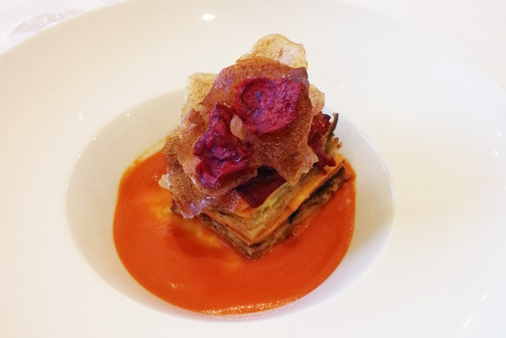 "The pasta course was a vegan lasagna layered with zucchini, butternut squash, eggplant, red pepper and a cashew ""cheese"" sauce. The base is tomato jus, and spiced beet and potato chips top it off."