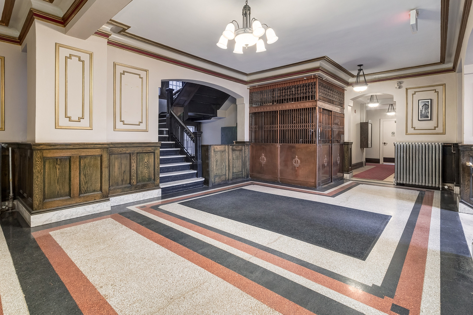 The elegant lobby includes a marble staircase and functional brass bird cage elevator.