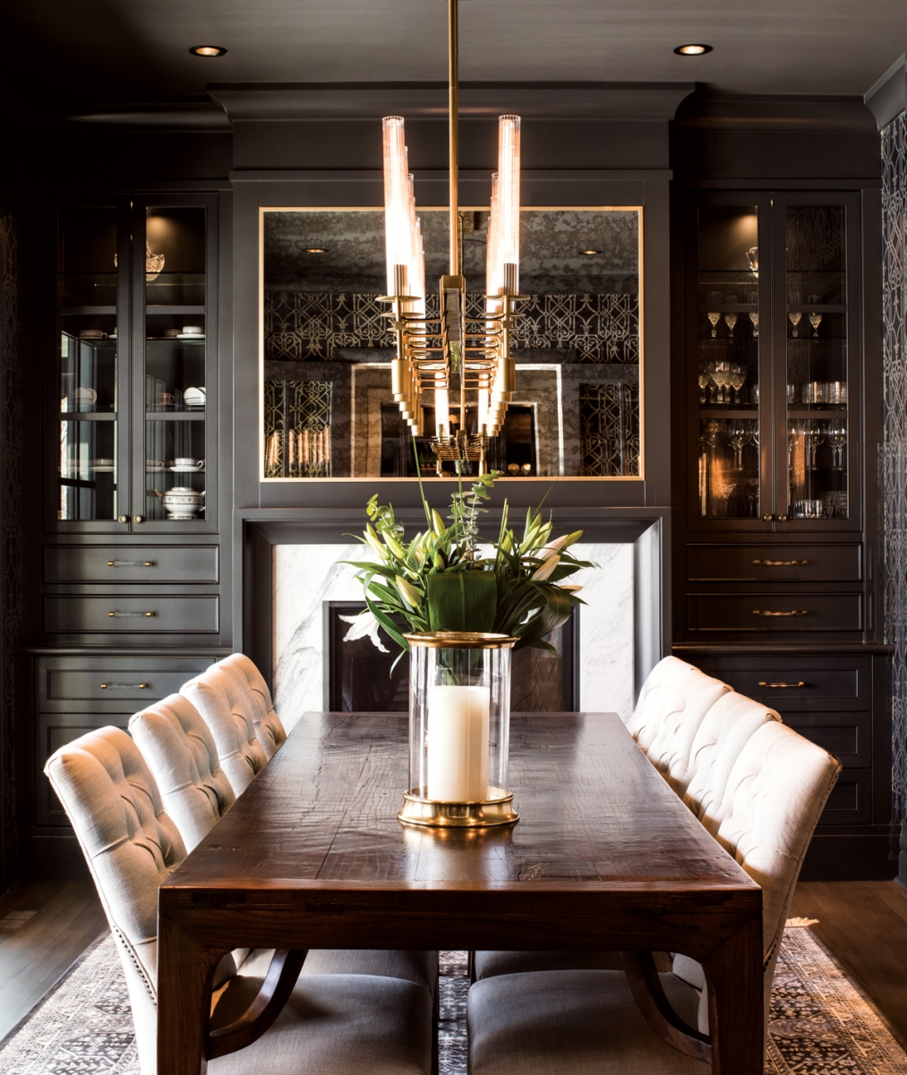 The dining room's traditional details, such as the smoked-glass mirror over the fireplace and antique table from Hinchcliff & Lee create a sense of timeless elegance.
