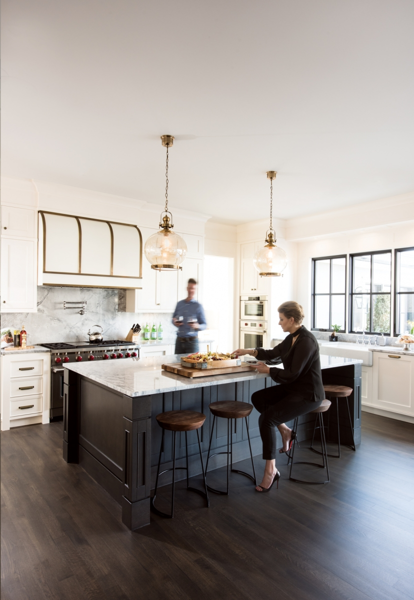 Homeowners Joanna Januszewska and Rafal Wieczorek in the kitchen of their home in Roxboro. The five-by-10-foot kitchen island is stained in a custom-created colour called Charcoal Mist, which was used throughout the home.