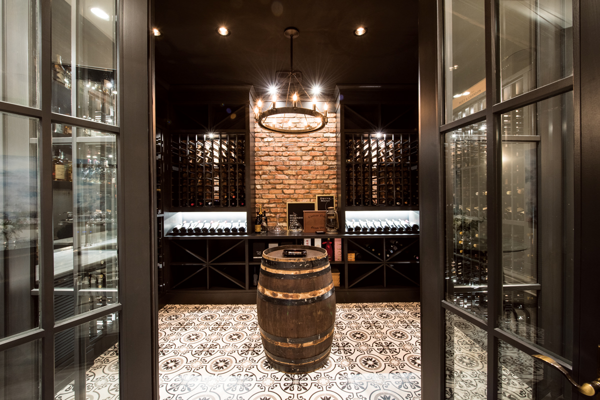 Perfect for holding tastings or smoking a cigar, the wine cellar/cigar room suggests an Old World European tavern with its tiled floor, cherry-wood shelving and a wine barrel imported from Italy used as a table.