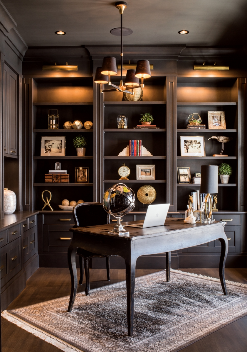 Januszewska's office features custom-made shelving displaying a curated collection of family photos and treasured mementos. The desk and chair are antiques paired with a new light fixture from Restoration Hardware.