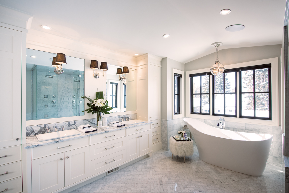 With its ample clean-lined vanity and herringbone-patterned Carrara-marble tile floor, the main ensuite is light and elegant with its oversized Aquabrass soaker tub and tufted stool. All electrical outlets are discreetly hidden within the cabinets.