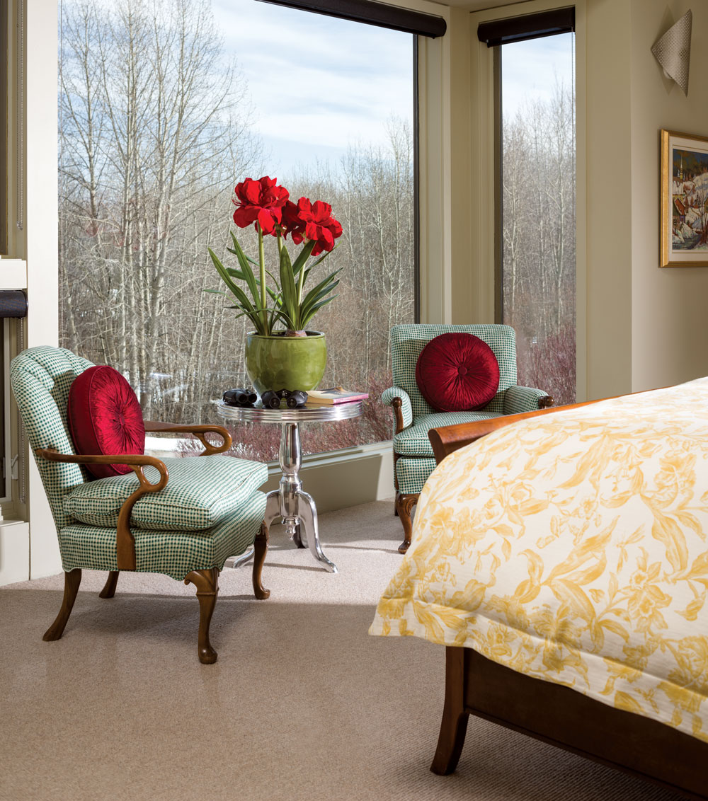 An expanse of windows in the master bedroom capitalizes on the private, natural surroundings.