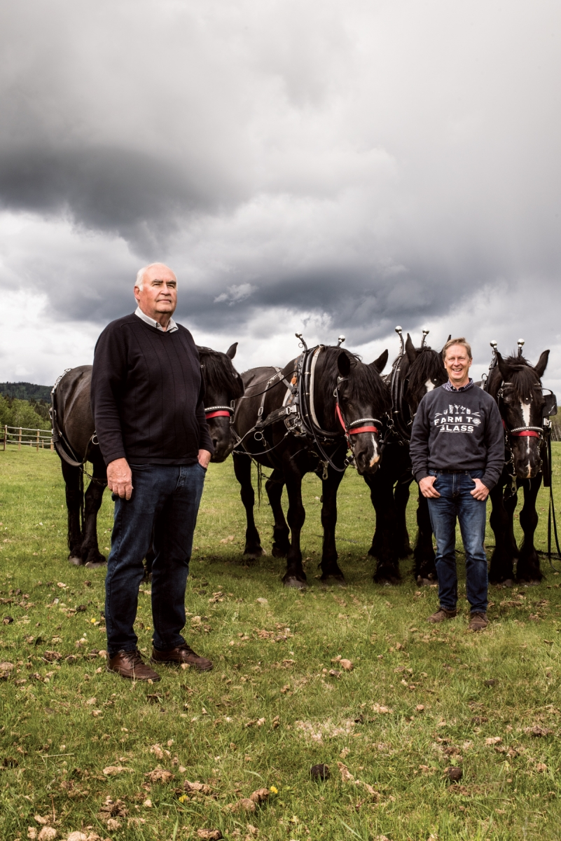 Eau Claire Distillery master distiller Larry Kerwin (left) and president and co-founder David Farran (right) with horses used in traditional farming practices to produce grains that are distilled into Eau Claire spirits.
