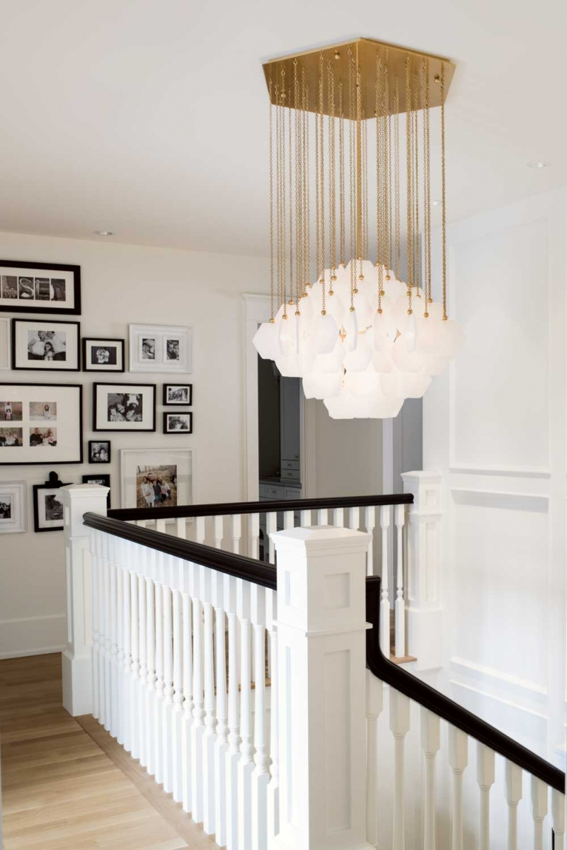 An eye-catching Jonathan Adler chandelier hung above the main staircase adds a touch of glamour to the upper hallway area.