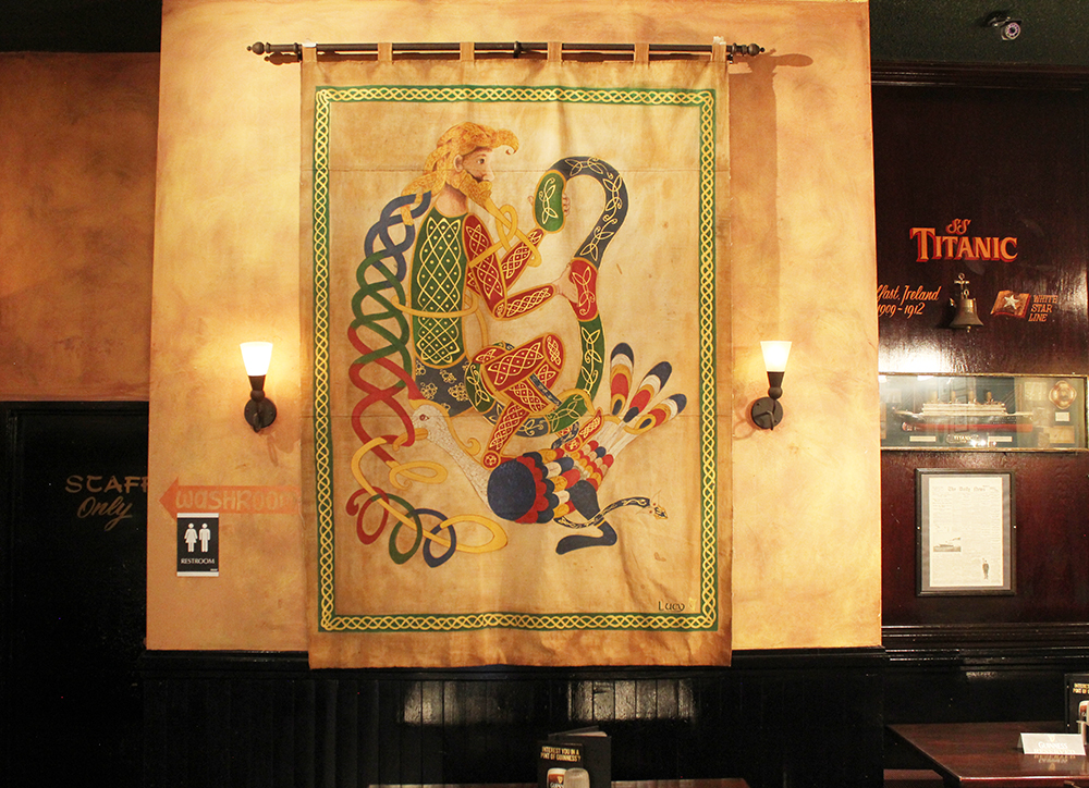 This and other tapestries hanging in the pub were created by a family friend from Ireland who now lives in Red Deer. She made them from old Boy Scout tents, coloured them with cold tea and fire and hand drew Celtic art from the Book of Kells, one of the world's oldest manuscripts held in Trinity University in Dublin. This tapestry is one of the illuminated letters from the Book of Kells.