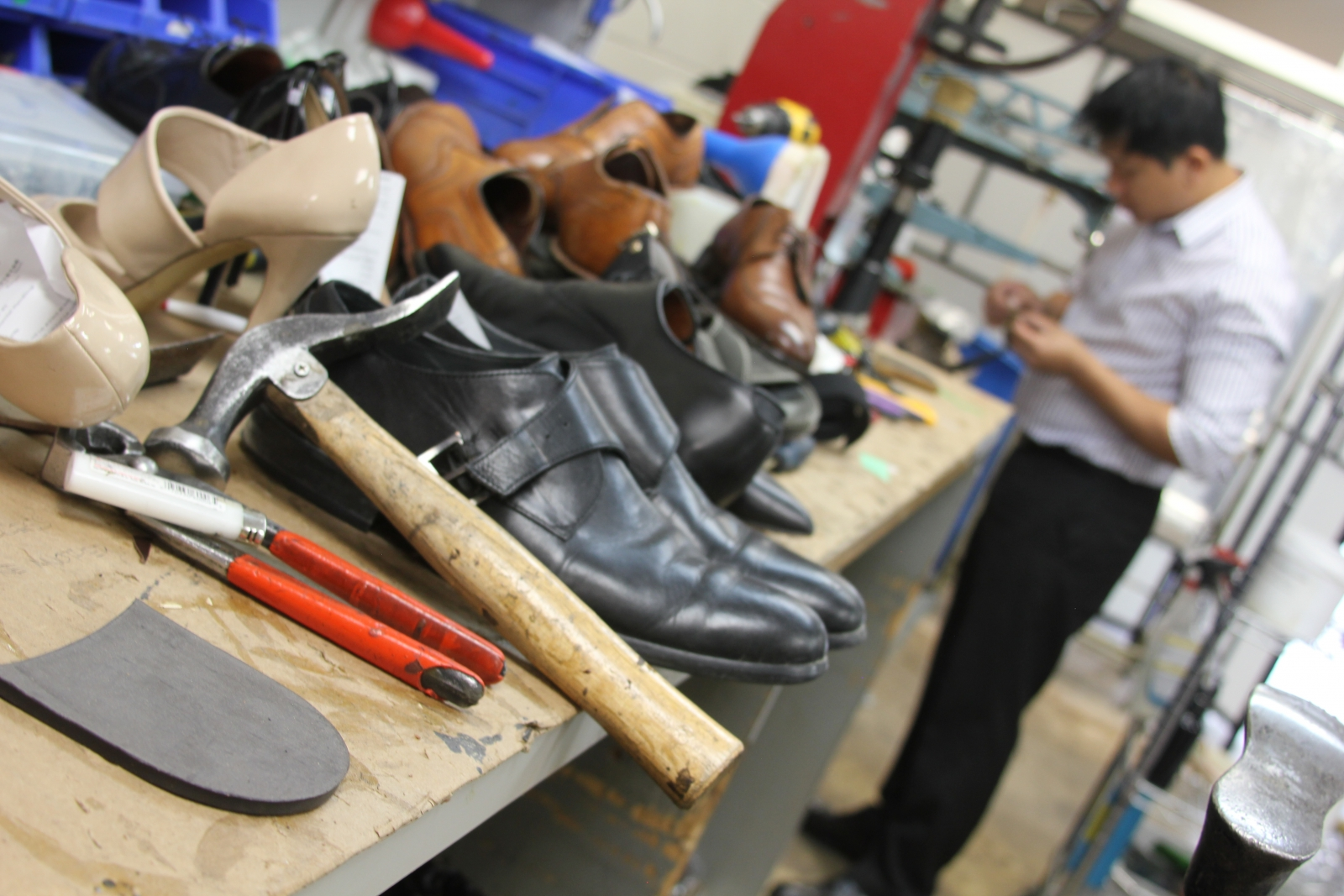 Tools of the trade are placed next to rows of shoes awaiting repair.