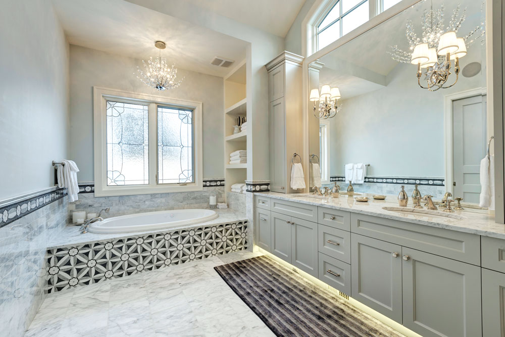 The principal bathroom is a spa-like retreat awash in a soothing palette of white and grey and intricate tile work.