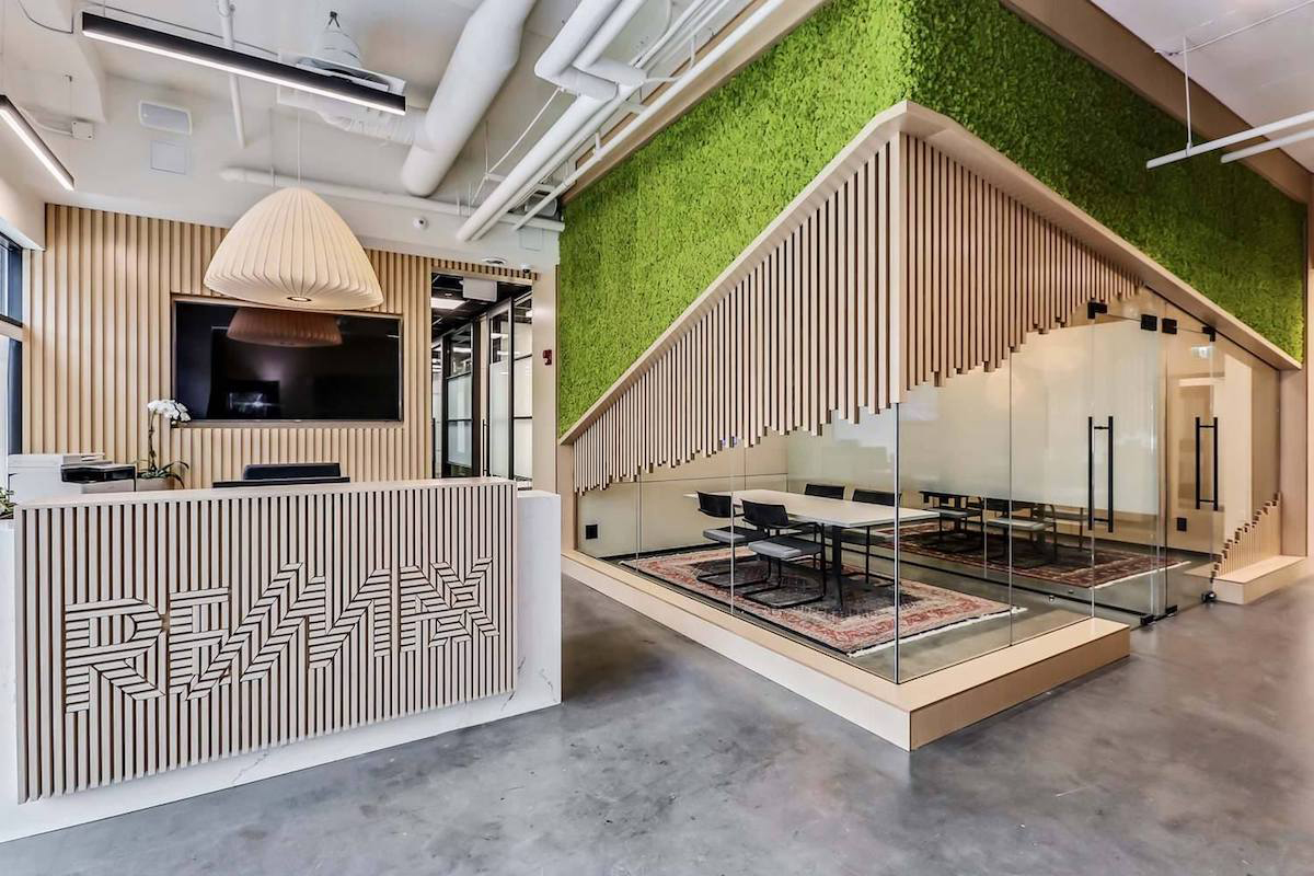 When you walk into the lobby of RE/MAX House of Real Estate, your eye is immediately drawn to the bright green moss wall. White oak slats partially cover the outside of meeting rooms and the reception area, subtly spelling out the company's name on the front desk.
