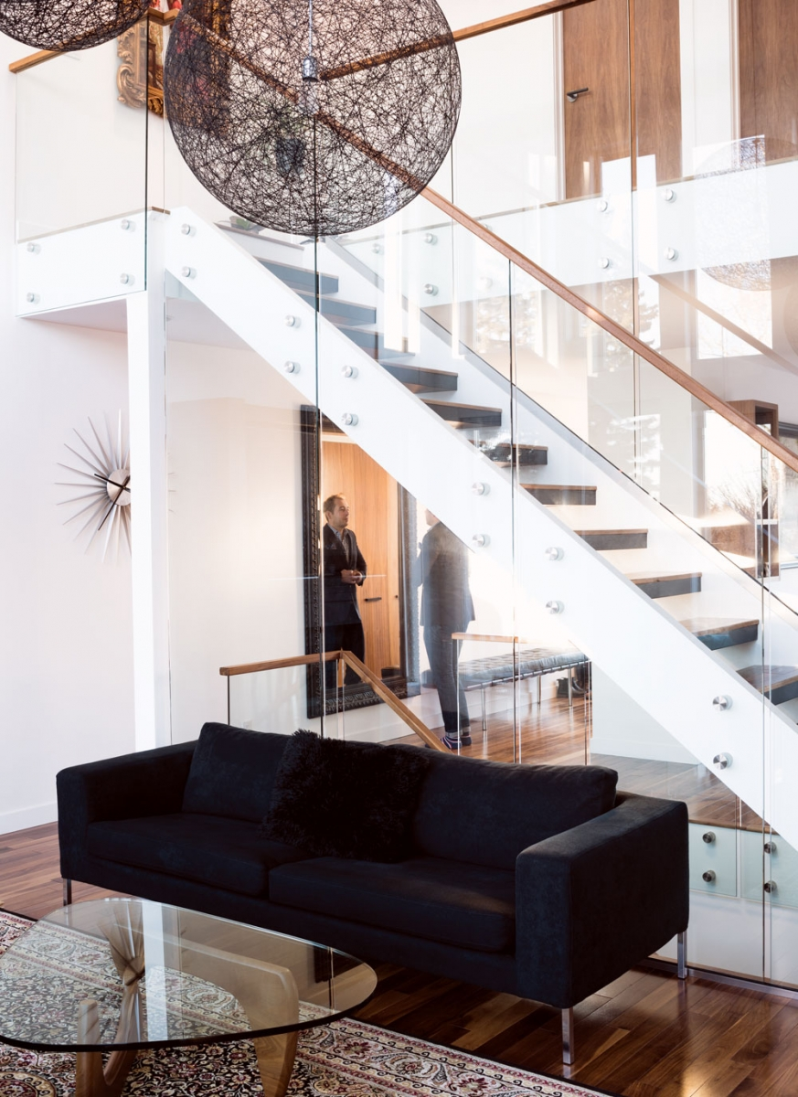 The home's open floor plan is punctuated by a glass-walled staircase.