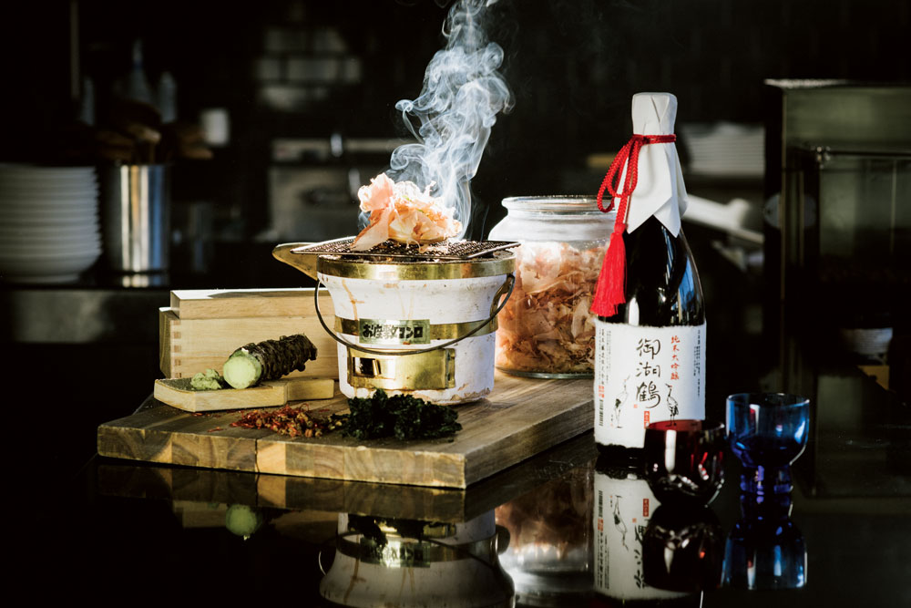 Scallop isoyaki, grilled tableside, with sake.