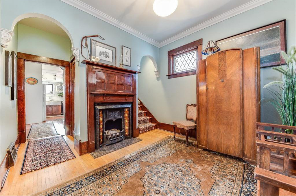 The entranceway has a fireplace with original woodwork and mantle.
