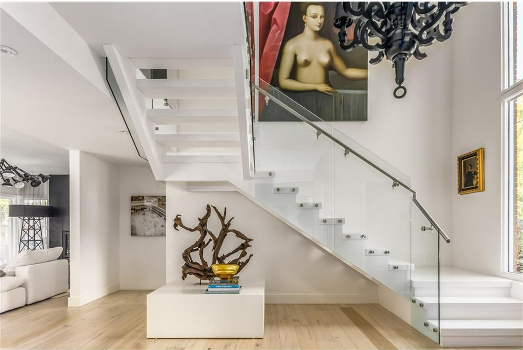 A matte black Moooi chandelier hangs over the glass staircase.
