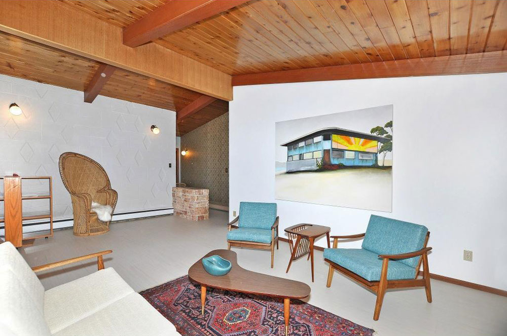 The living room has an original wood-paneled ceiling and cement feature wall, as well as new Marmoleum flooring.