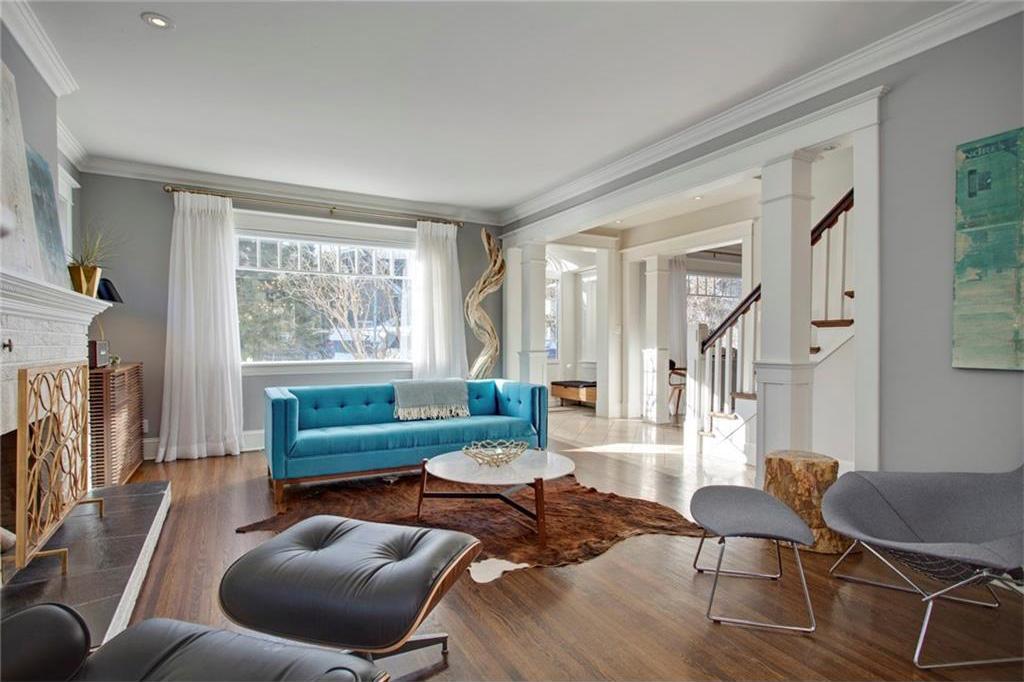 The sunny living room has original hardwood and an original wood burning fireplace.