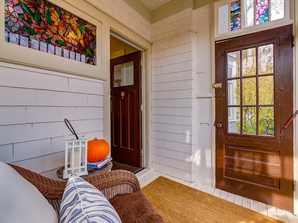 The enclosed front porch has striking stained glass windows.
